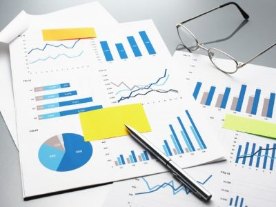 Reviewing financial reports. Graphs and charts. Business reports, documents, glasses and pen.
