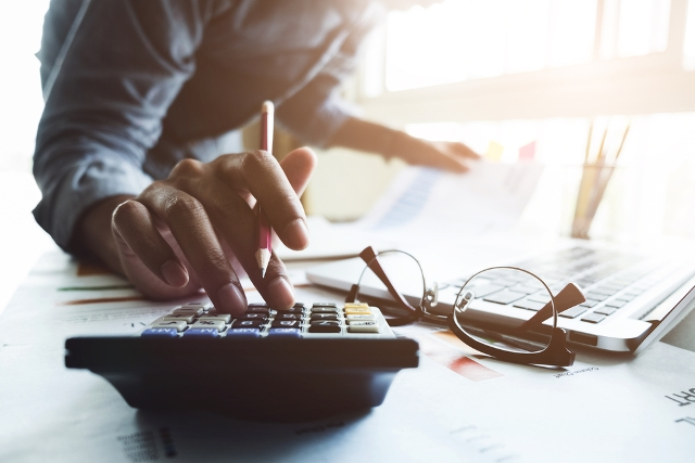 Close up of businessman or accountant hand holding pen working on calculator to calculate business data, accountancy document and laptop computer at office, business concept.